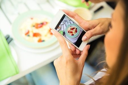 44438270 - portrait of a woman making photo of food on smartphone in restaurant